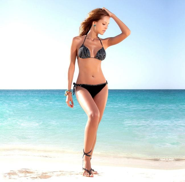 Девушка в черном бикини на берегу моря