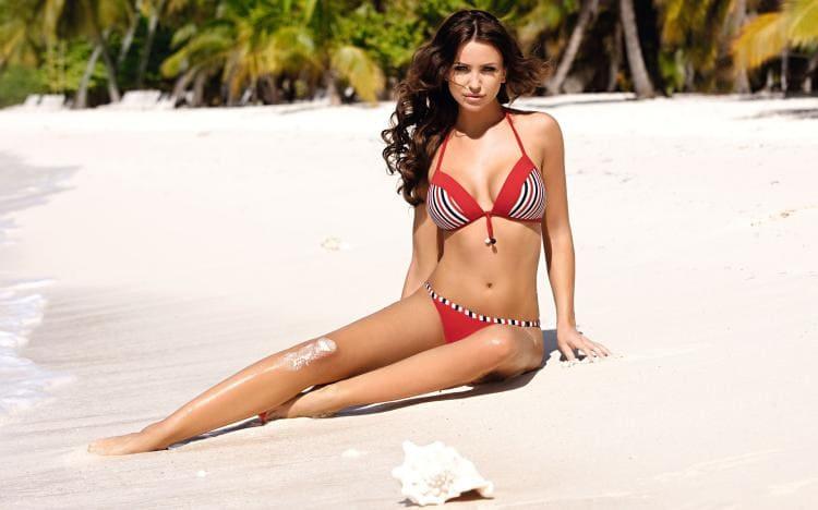 В красном купальнике красивая брюнетка с длинными волосами сидит на песке