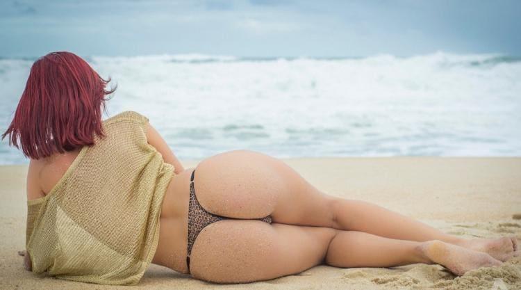 Лежит на берегу моря, вид сзади в бикини