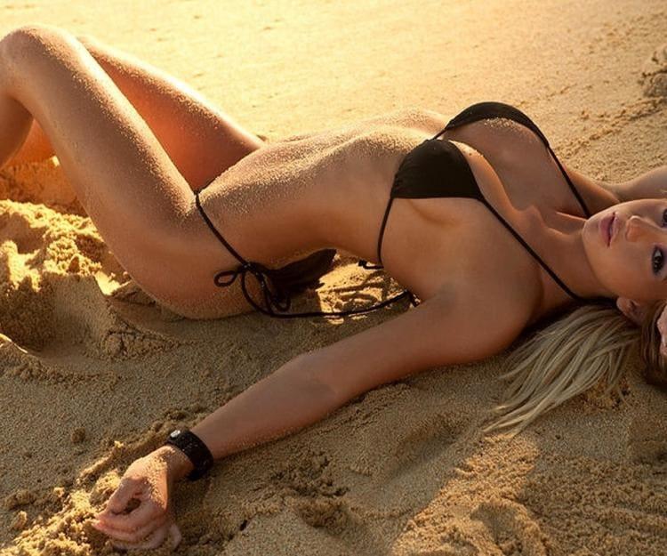 Красивая загорелая блондинка в черном бикини изогнувшись лежит на песке