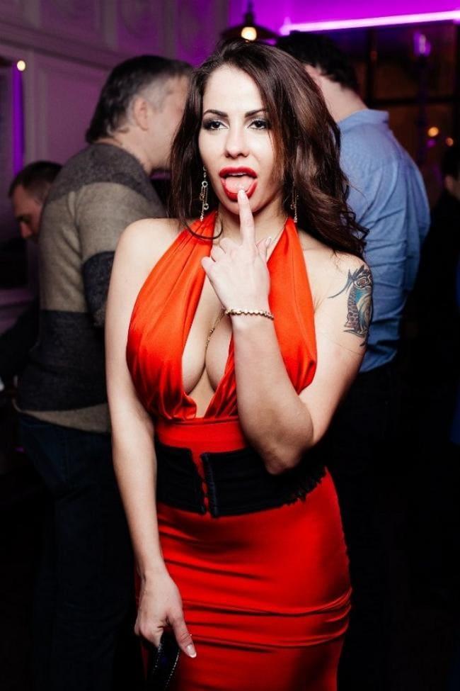 В красном платье с большим декольте облизывает палец