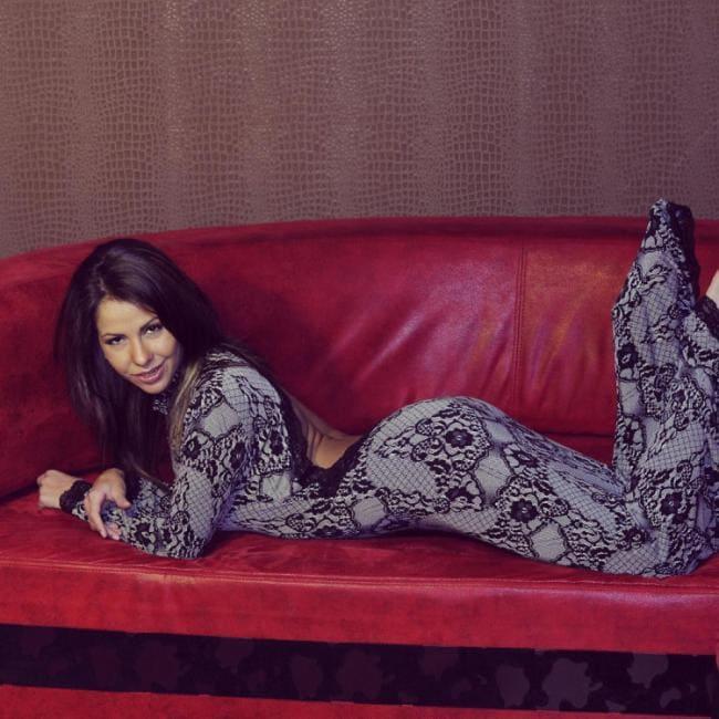 В брючном костюме лежит на красном диване