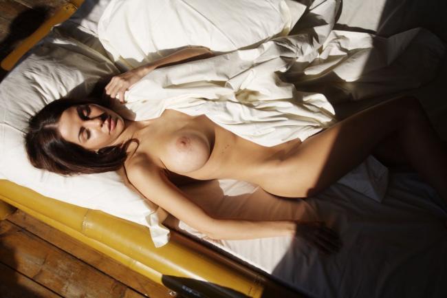 Голая лежит на спине слегка прикрывшись простыней