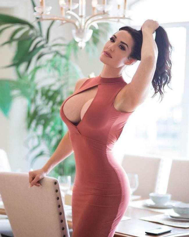 Шикарная брюнетка в обтягивающем платье с большой грудью