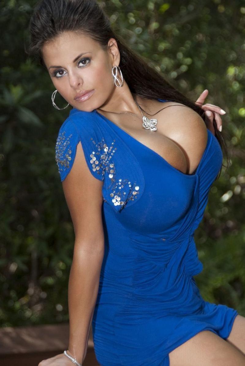 большие сиськи в синем платье девушка сидит немного прогнувшись, длинные темные волосы распущены, на шее большой кулон, в ушах крупные серьги в виде восьмерки