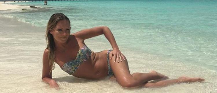 В купальнике лежит на боку песок вода