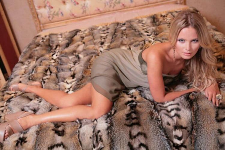 Лежит на кровати в сером платье, босоножки на высокой платформе