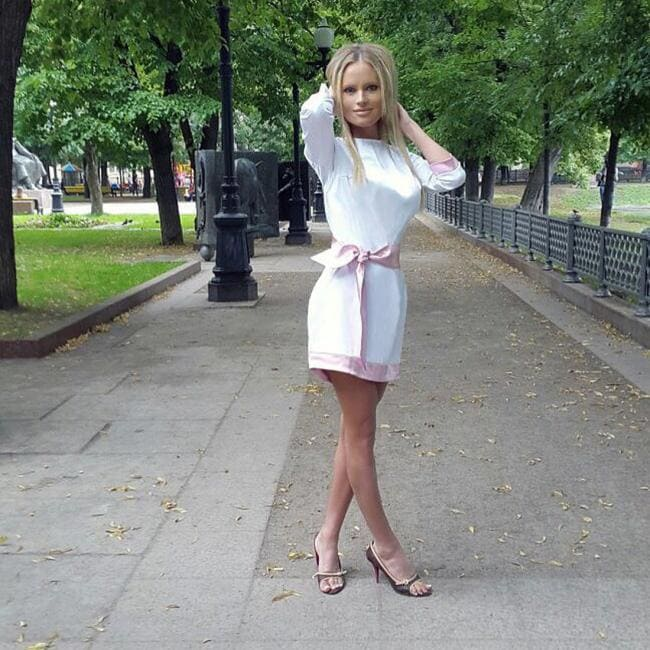 В белом коротком платье стоит