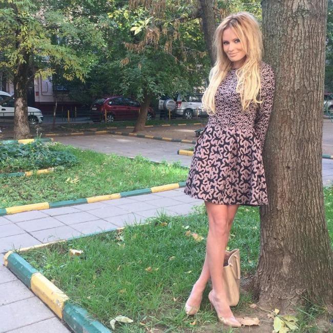 В коротком платье стоит возле дерева