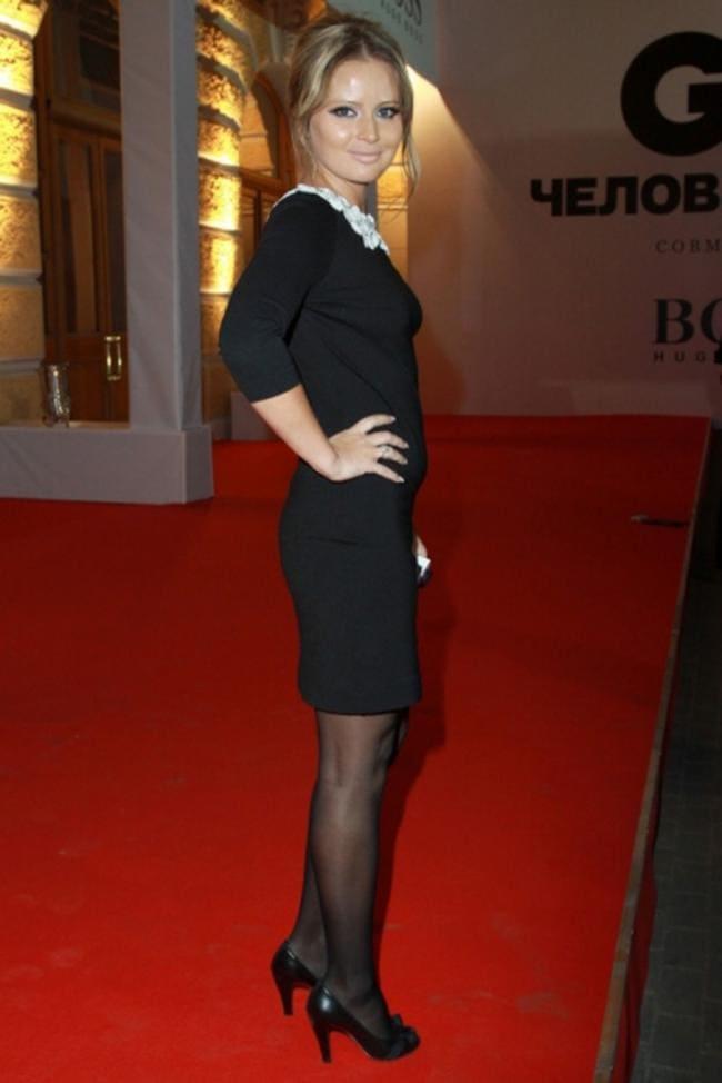 Стоит боком в черном коротком платье черные колготки, туфли на высоком каблуке