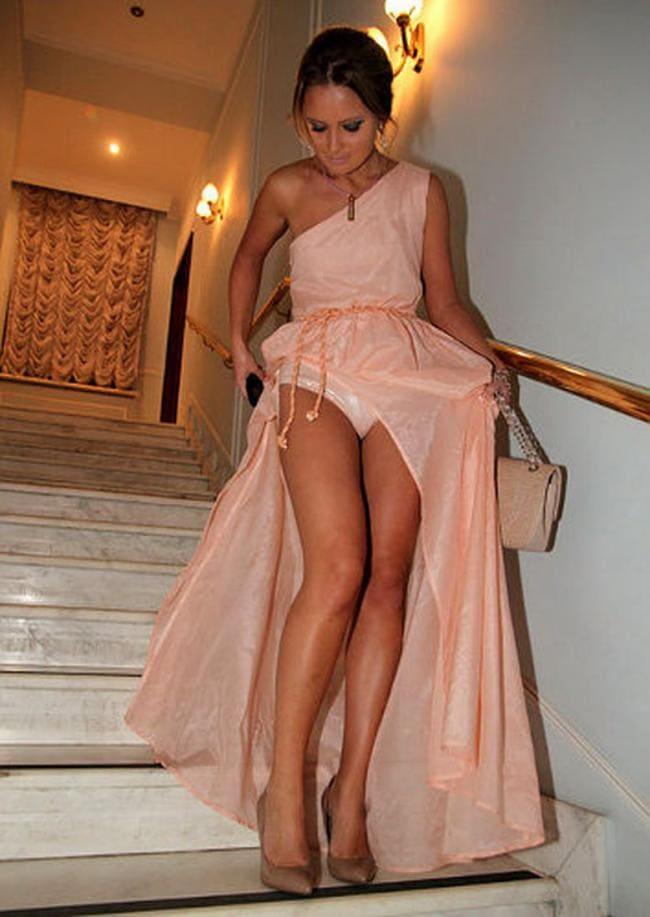 Спускается по лестнице в длинном розовом платье, которое подняла так, что видны трусы