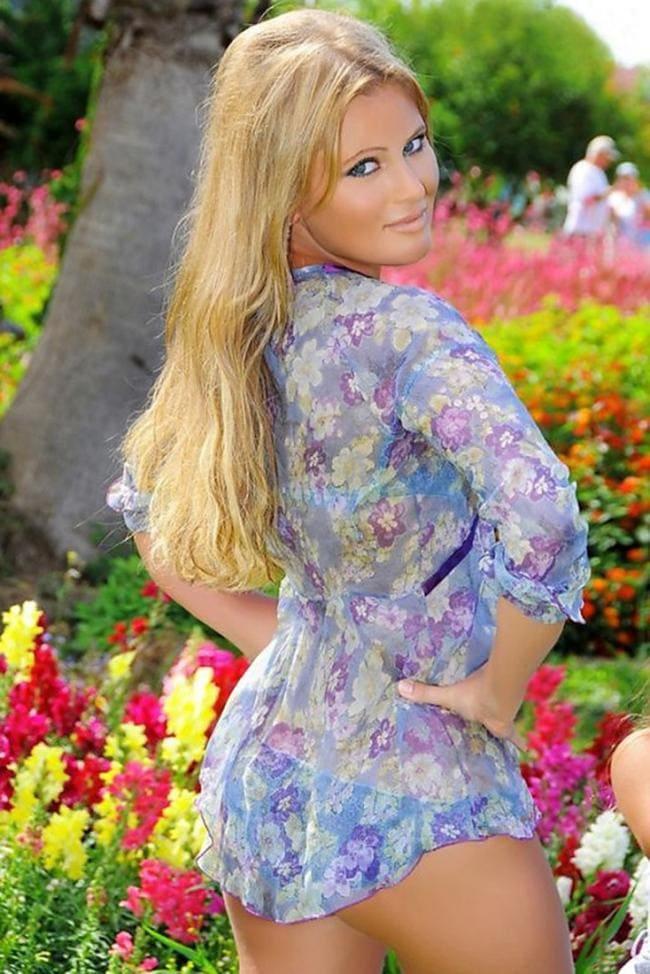 Дана Борисова в короткой цветастой кофточке стоит спиной