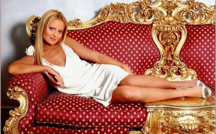 В белом платье с глубоким декольтеполулежит на красном диване
