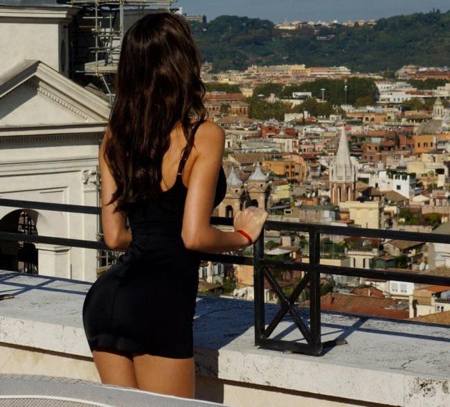 В черном мини платье стоит ,вид со спины