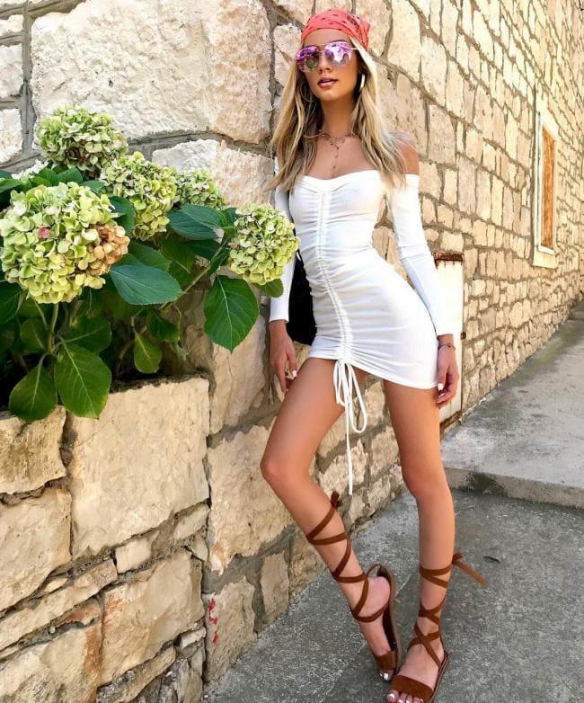 Белое платье короткое с банданой на голове стоит блондинка с длинным волосом, босоножки ножки