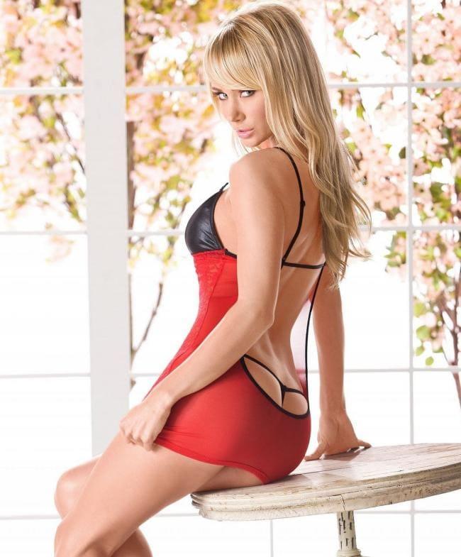 В коротком сексуальном платье сидит на столе вид сбоку