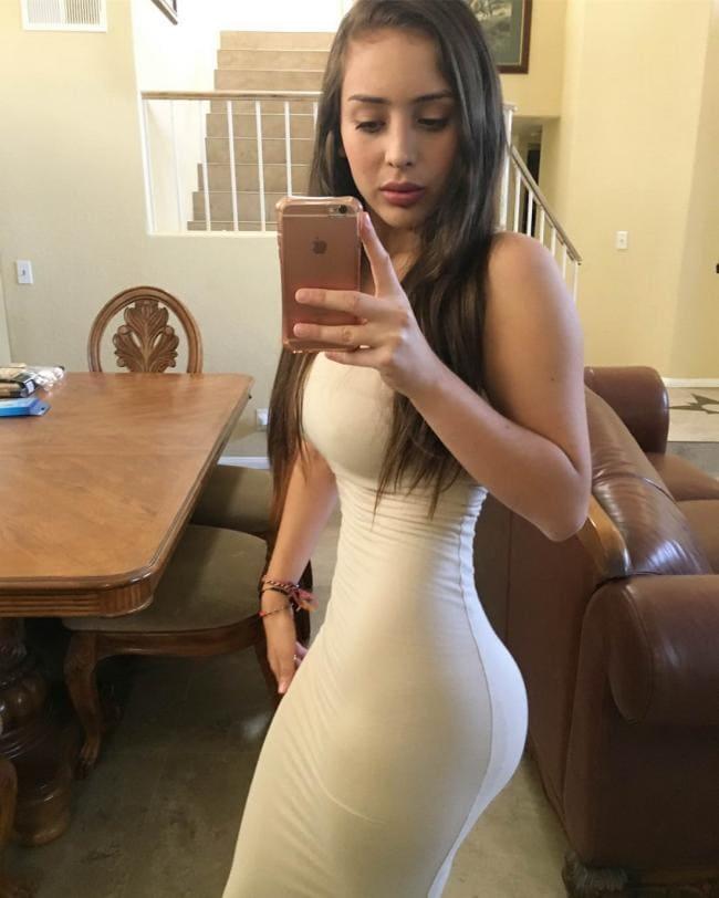 Стоит боком в обтягивающем платье с айфоном