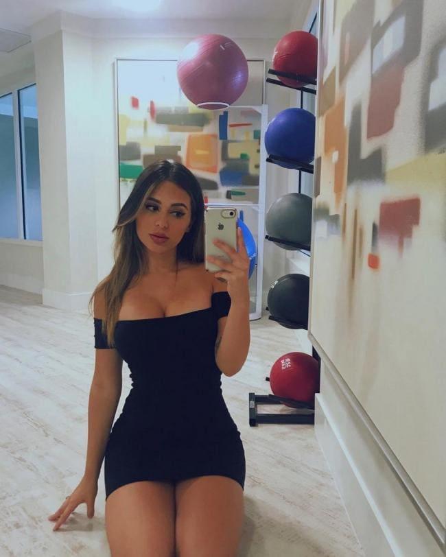 Черное короткое с глубоким декольте платье сидит на полу