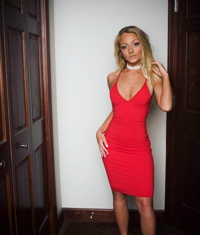 Девушки в обтягивающих платьях мини. Блондинка в красном платье с длинным волосом стоит, глубокое декольте