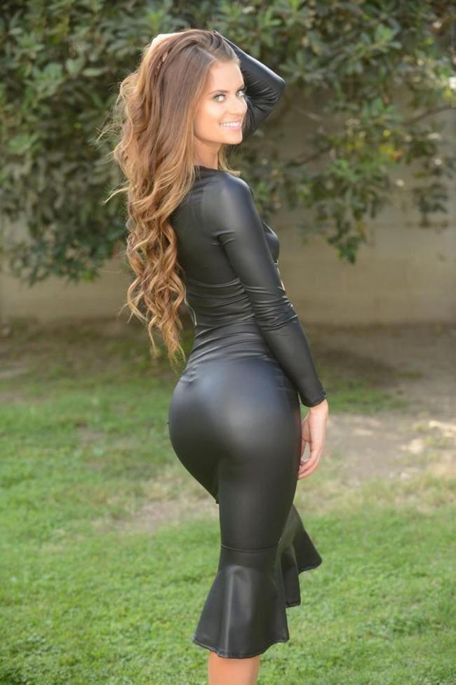Шикарная девушка с длинным волосом в черном платье вид сбоку