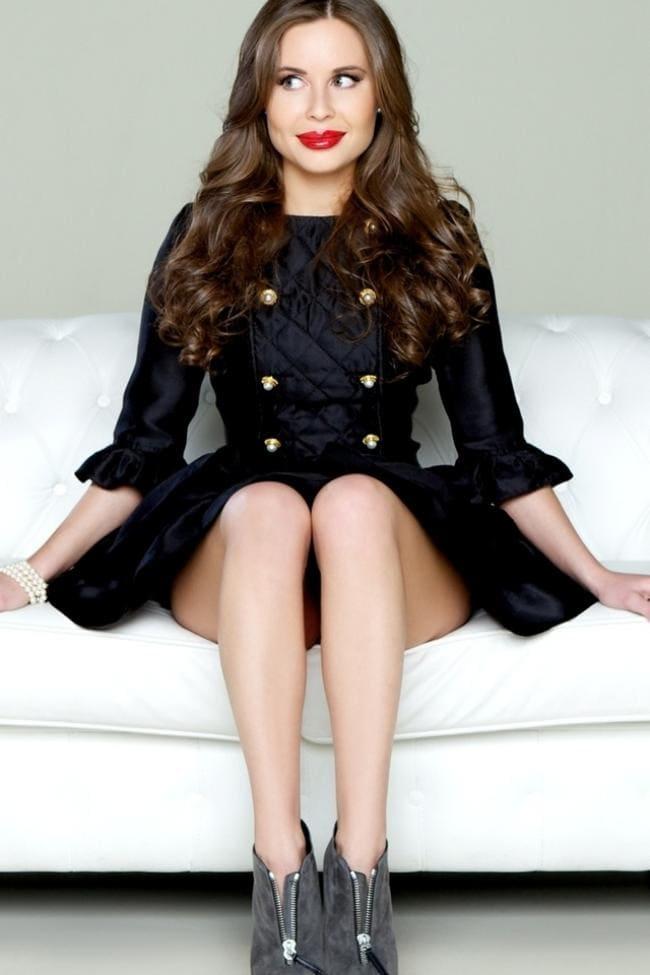 В черном коротком платье сидит на диване ножки каблук, вид снизу