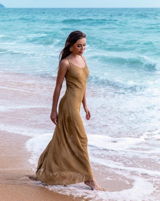 В длинном облегающем платье без нижнего белья босая идет по берегу моря