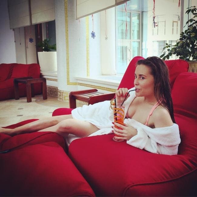 Лежит на красном диване в распахнутом халате ,сосет коктейль