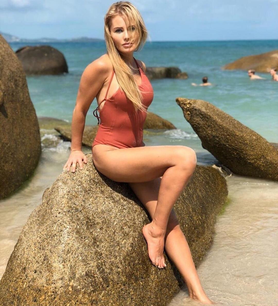 Дана Борисова фото в сплошном купальнике кораллового цвета сидит на камне на берегу моря, левая нога согнута в колене