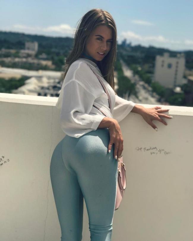 В обтягивающих брюках стоит повернувшись попой