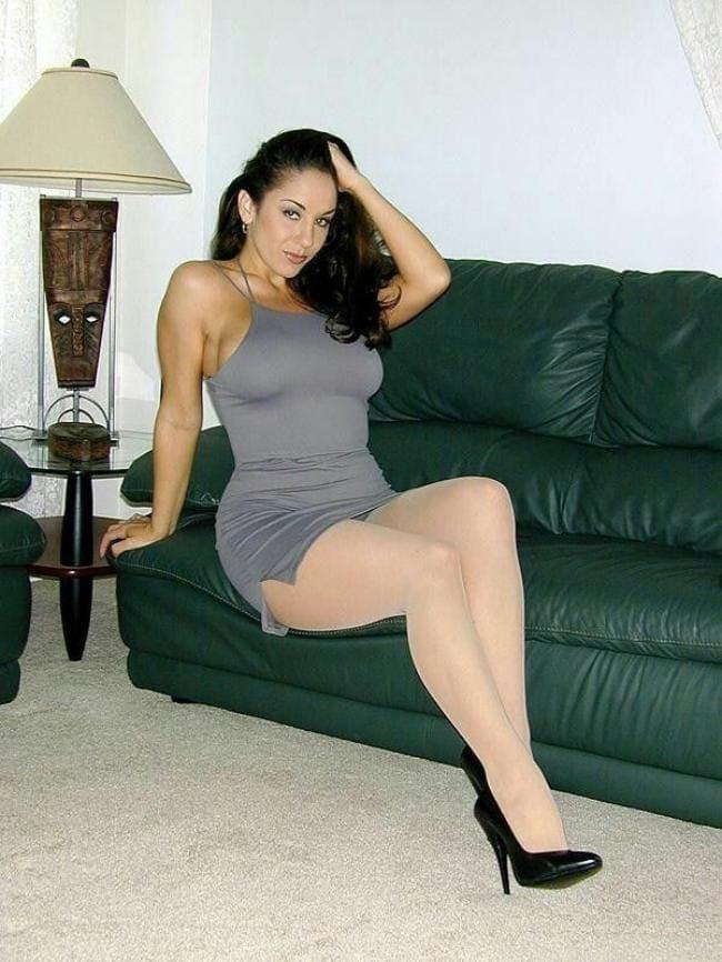 Красивая зрелая брюнетка в коротком платье серого цвета сидит на диване в колготках и туфлях на высоком каблуке
