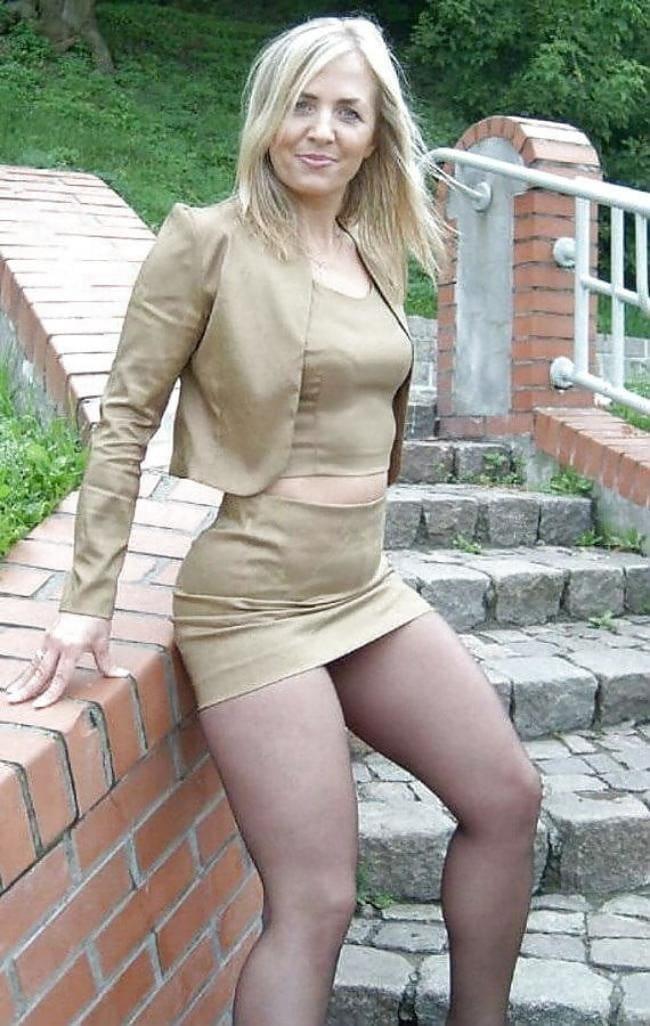 зрелые женщины в очень короткой юбке блондинка немного расставила ноги в колготках опирается на кирпичный забор, волосы распущены