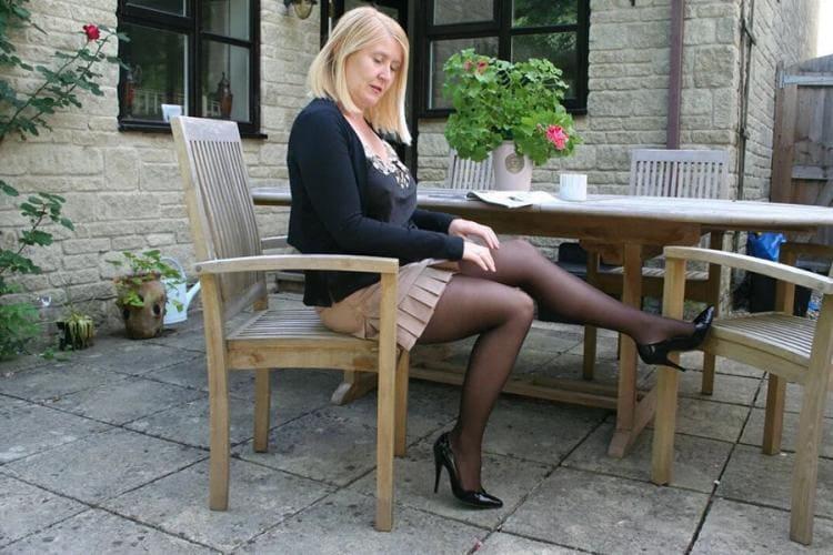 милфа в юбке фото cидит на стуле зрелая за 50 в черных колготках, туфли на каблуке, ножки показывает