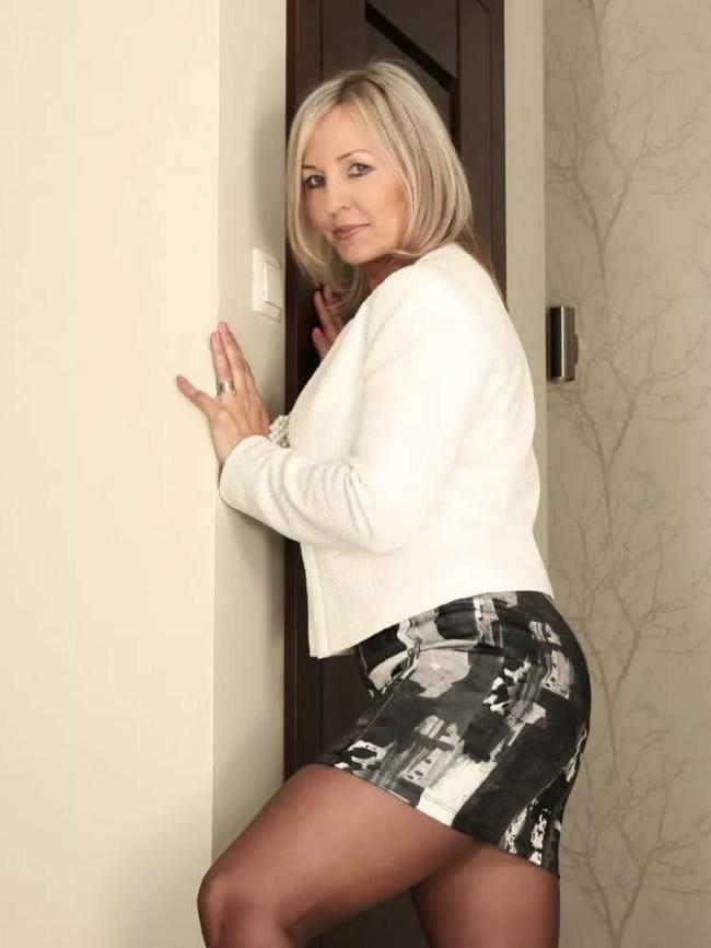 Зрелая блондинка в колготах в короткой юбке стоит боком