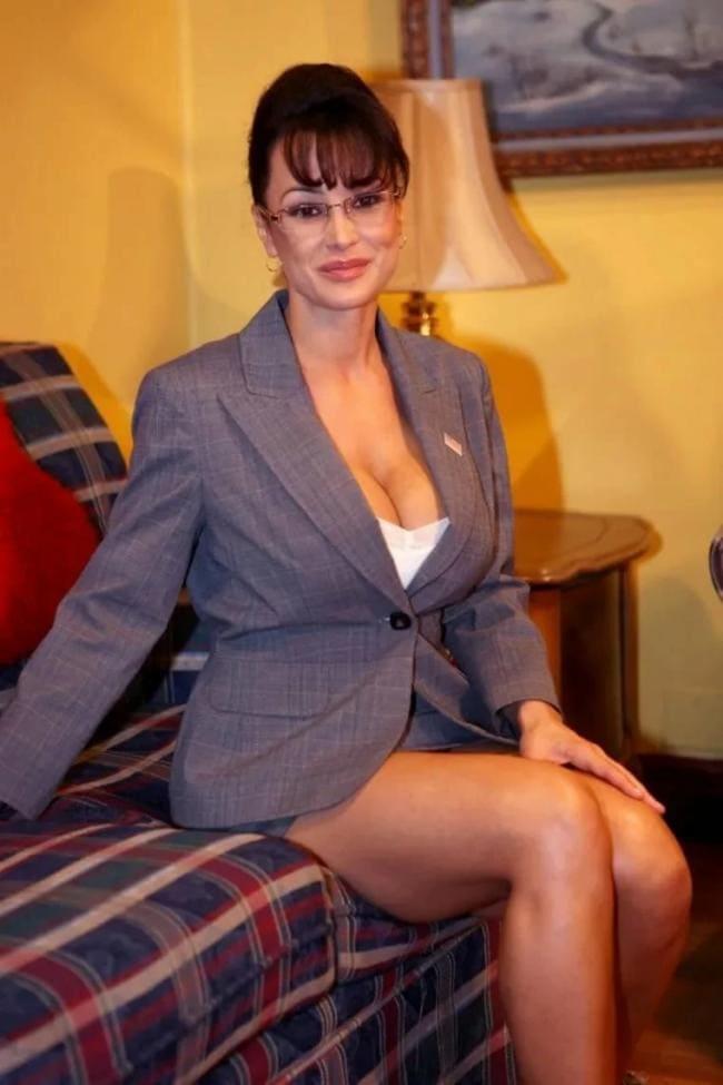 зрелые в коротких юбках в деловом костюме, в очках, сидит на диване высоко задрав юбку, ноги голые