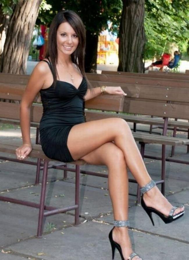 Красивая брюнетка в черном коротком платье сидит показывает свои чудесные ножки на каблуках