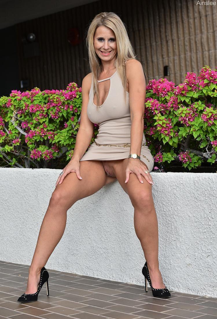 Женщины в коротких юбках фото красивой милфы которая раздвинула ноги и показывает голую пизду, на ногах черные туфли на каблуке, руки лежат на коленях сама сиди на клумбе с цветущими красными цветами, русые волосы распущены, улыбается похотливо