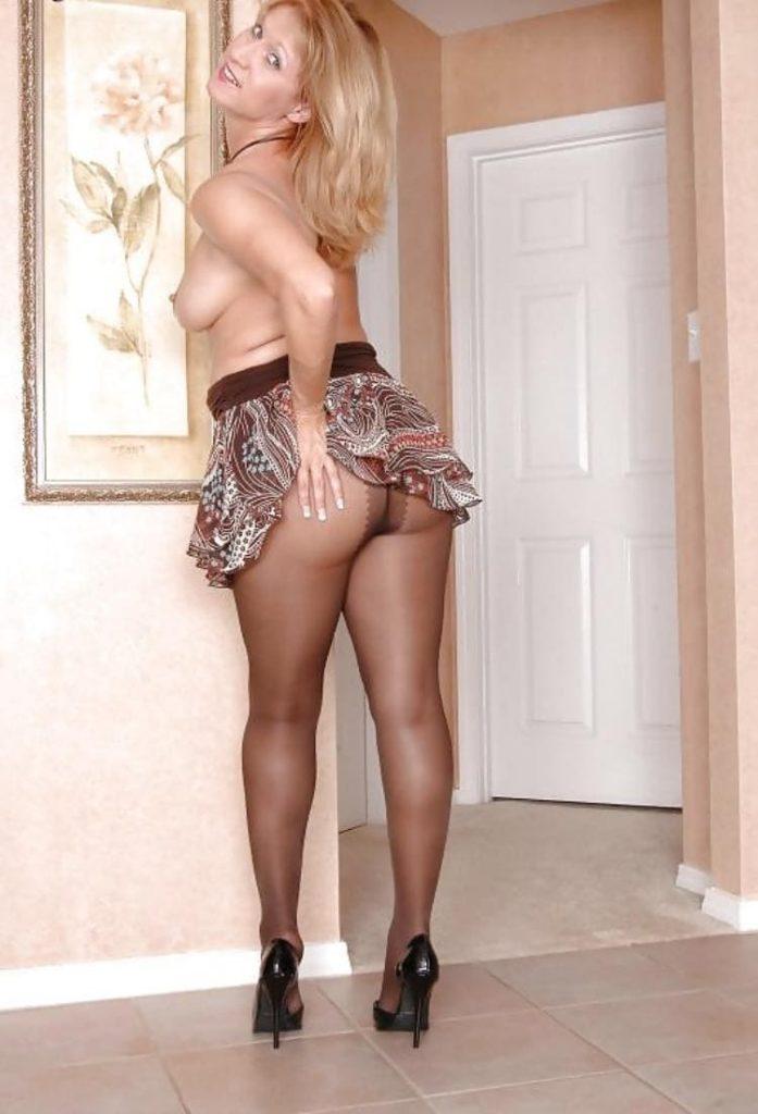 Фото женщин в коротких юбках милфа стоит с голым торсом демонстрируя голую сиську, приподняв юбку рукой показывая левую часть жопы в черных колготках, на ногах черные туфли на шпильке, слегка изогнулась и облокатилась на стену с картиной