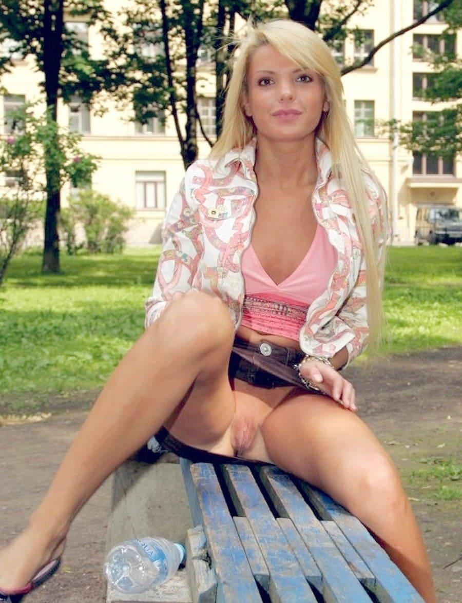Красивая зрелая блондинка сидит на лавочке во дворе и задрала юбку показывая бритую пизду, в розовой кофточке с глубоким декольте, взгляд прямой развратный.