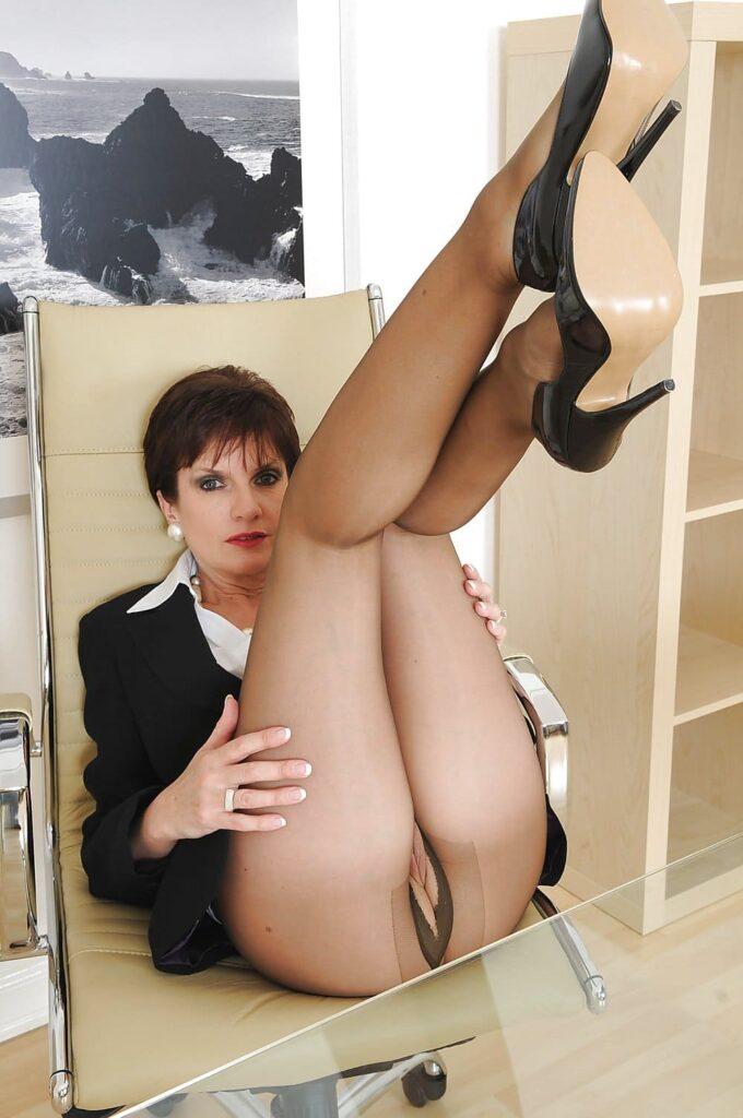 Красивая зрелая женщина задрала короткую юбку и подняла красивые стройные ноги в черных колготках и без трусов поэтому просвечивается пизда лежа в белом офисном кресле, стрижка короткая, на ногах черные туфли на каблуке.
