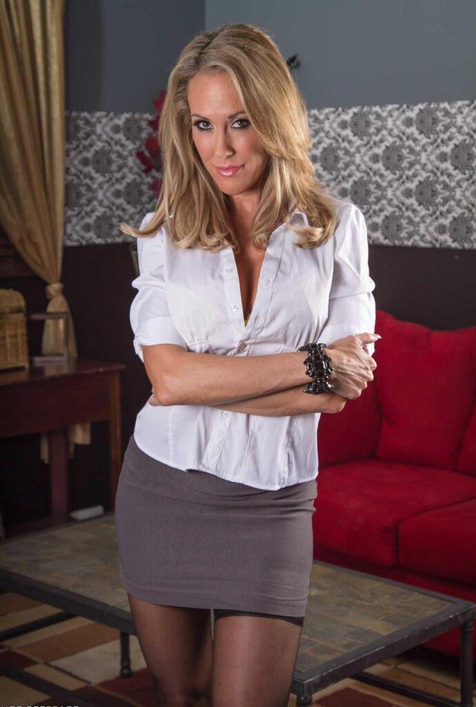 зрелые в коротких юбках красивая блондинка в белой кофточке немного расстегнутой, темных колготках стоит кокетливо улыбается