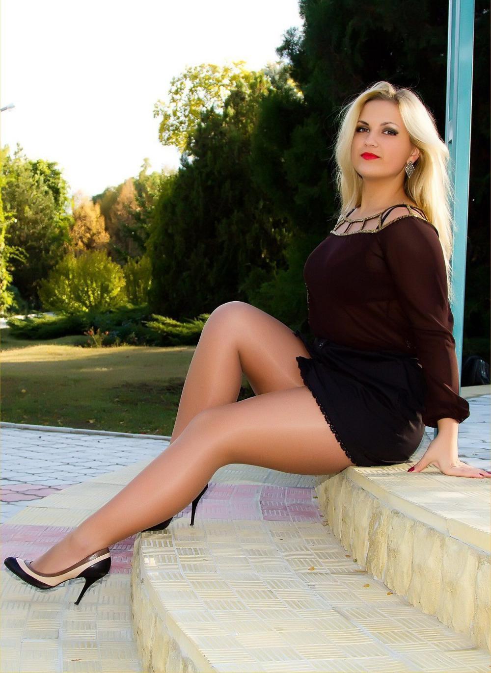 зрелые в коротких юбках блондинка с распущенным длинным волосом сидит на ступеньках в арке ножки шикарные в светлых колготках и туфли на высоком каблуке