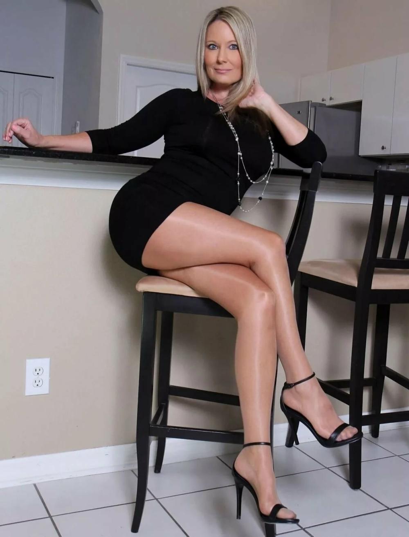 зрелые в коротких юбках красивые длинные ноги в открытых черных открытых босоножках и светлых чулках сидит на высоком стуле