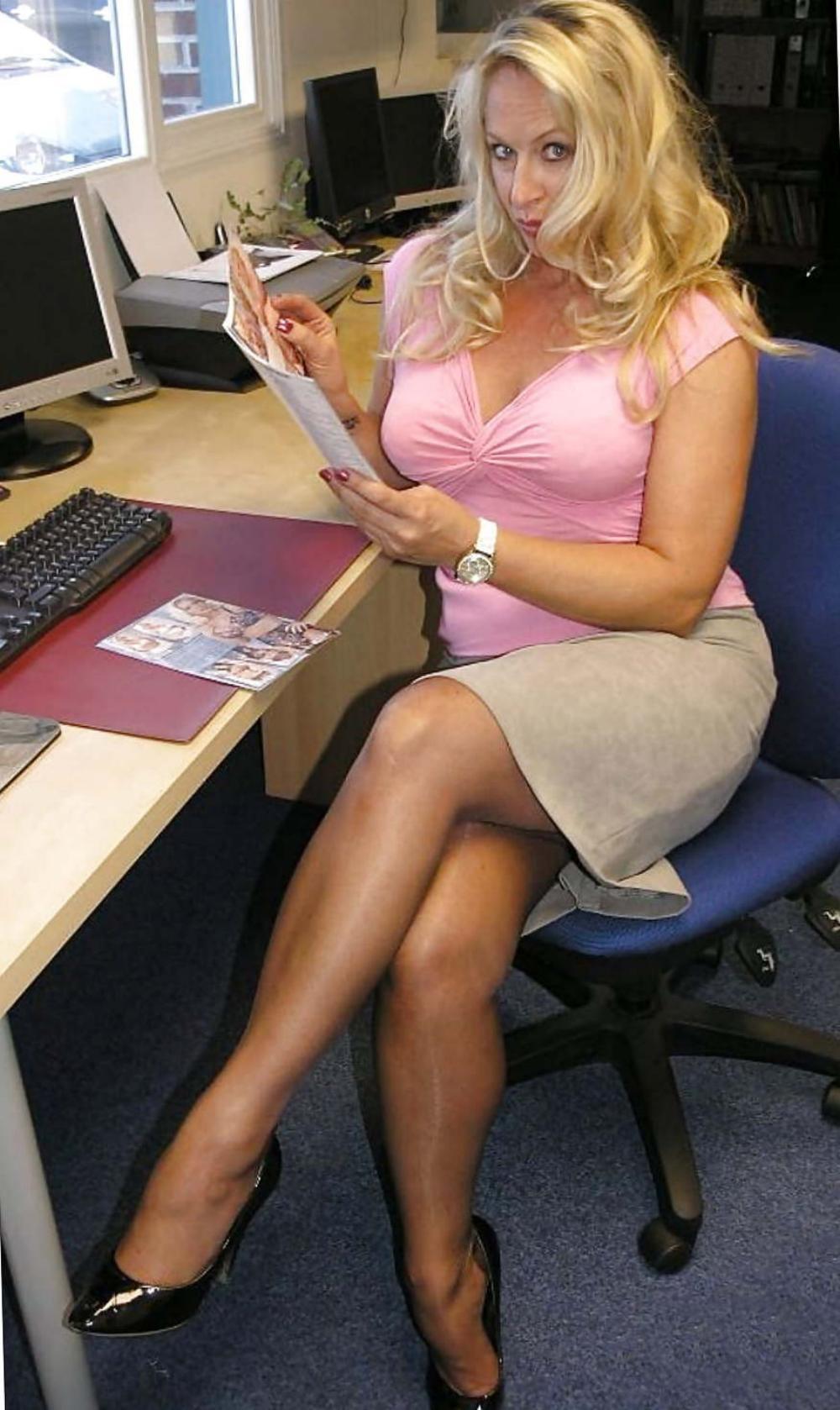 зрелые в коротких юбках в розовой кофточке с глубоким декольте, сидит нога закинута за ногу, туфли на каблуках