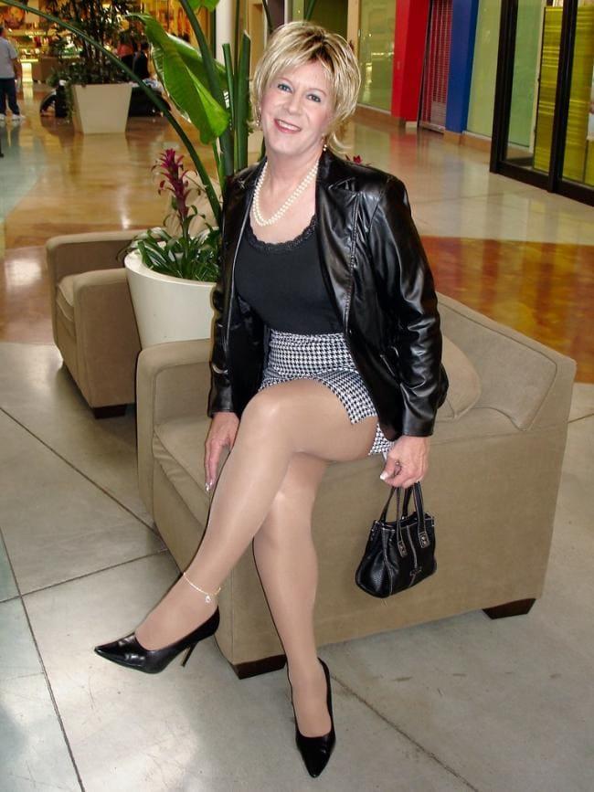 Зрелая блондинка сидит на кресле показывая свои ножки на голени одет браслет