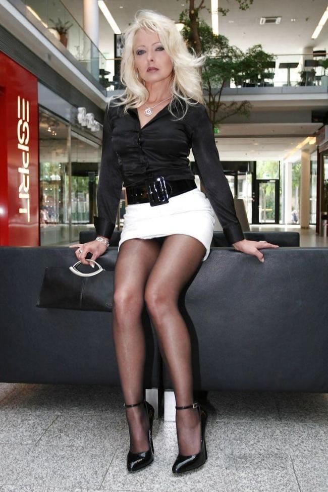 Шикарная женщина под 50 в короткой черной юбке черном капроне туфли на высоком каблуке с пряжкой