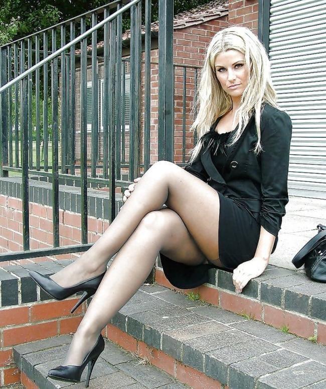 Красивая блондинка сидит на ступенях показывая свои ножки в ирнком капроне и туфли на высоком каблуке