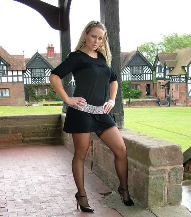В черном коротком платье стоит в чулочках и туфлях