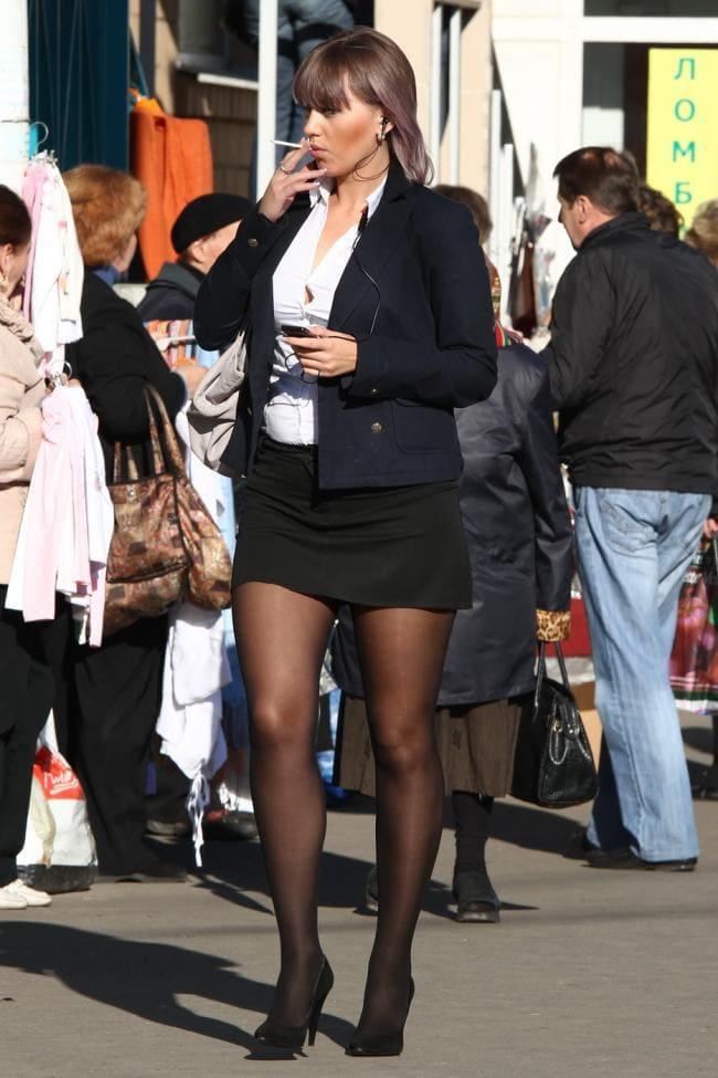 Женщина зрелая в короткой юбке, черных колготах и туфлях стоит курит на улице