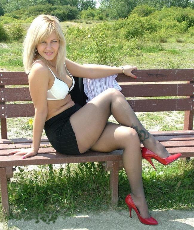 Красивая блондинка средних лет сняла кофточку сидит вполоборота на лавочке в тонком капроне на левой голени тату