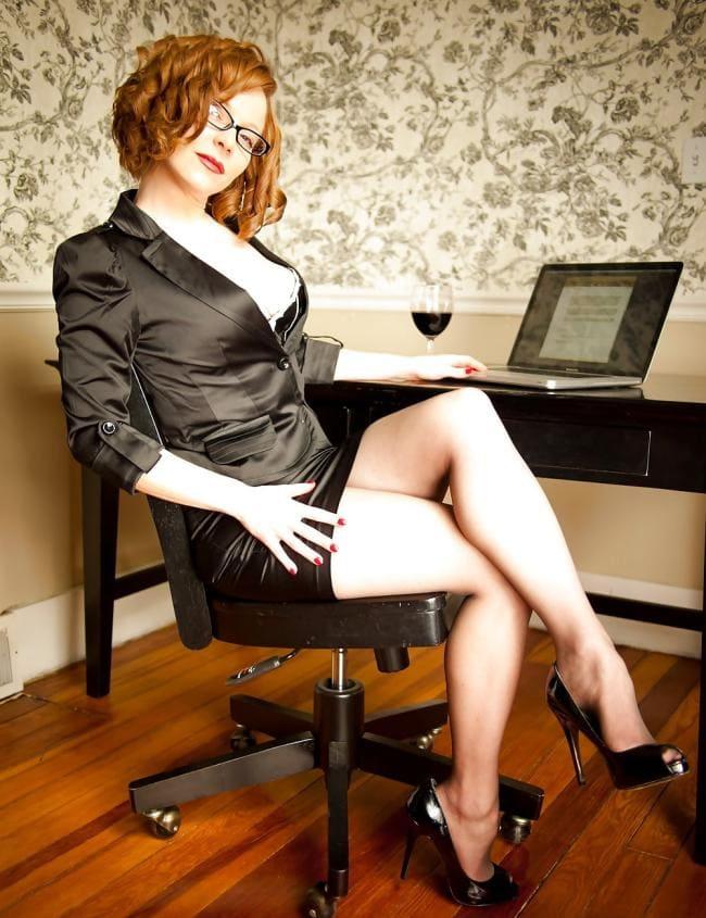 Красивая рыжая за 40 в очках сидит на стуле приподняв юбочку показывая свои красивые ножки обутые в туфли на шпильке
